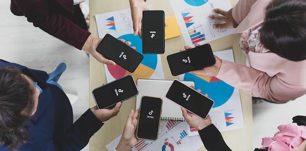 Bangkok/thaïlande - 6 août 2021 : les gens détiennent des smartphones de différentes marques et divers systèmes d'exploitation avec les logos tiktok, l'un des réseaux sociaux vidéo les plus populaires.
