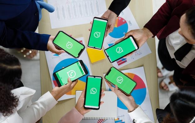 Bangkok/thaïlande - 6 août 2021 : les gens détiennent des smartphones de différentes marques et divers systèmes d'exploitation avec les logos de whatapp, les applications de messagerie populaires des réseaux sociaux.