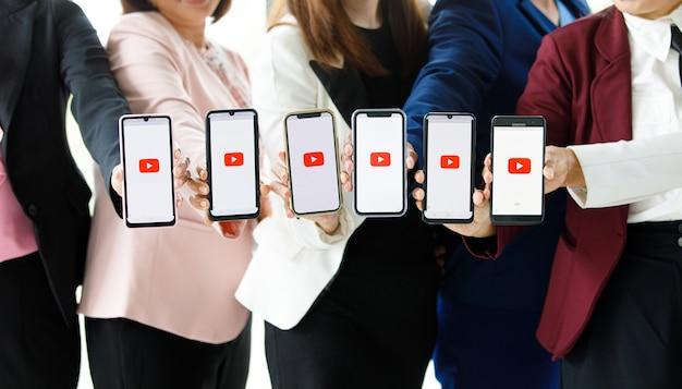 Bangkok/thaïlande - 6 août 2021 : les gens détiennent des smartphones de différentes marques et divers systèmes d'exploitation avec des logos youtube, le portail vidéo le plus populaire au monde.