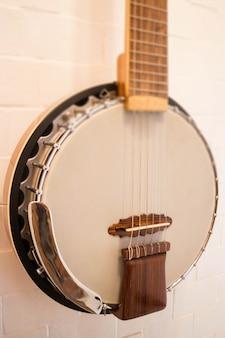 Banjo accroché au mur de briques blanches