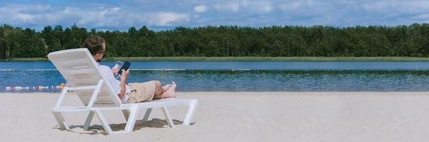Banner, un homme est allongé sur une chaise longue et charge un smartphone à partir d'une banque d'alimentation sur la plage. sur fond de sable, d'eau et de forêt.