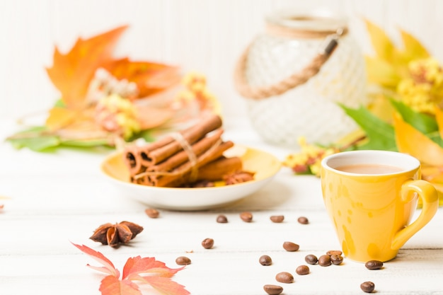 Bannière d'automne avec une tasse de café à la cannelle sur bois blanc