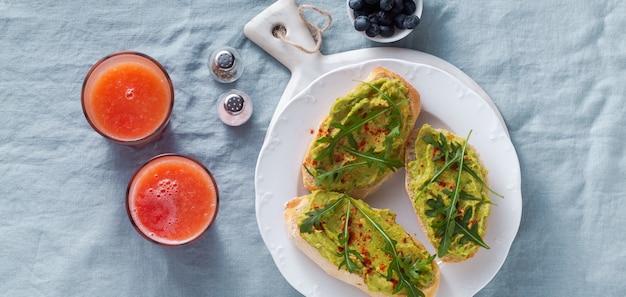 Bannière d'avocat et sandwich à la roquette avec du paprika sur la table. petit-déjeuner sain ou collation sur une assiette sur une nappe en lin bleu et jus de pamplemousse fraîchement pressé