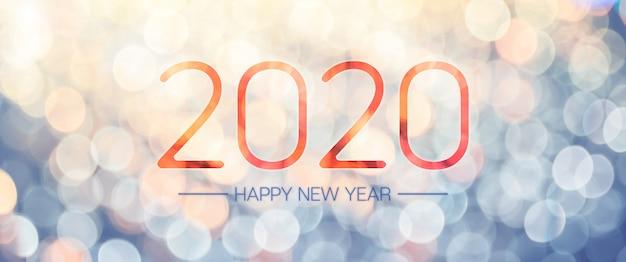 Bannière de bonne année 2020 avec des lumières de bokeh jaune et bleu pâle