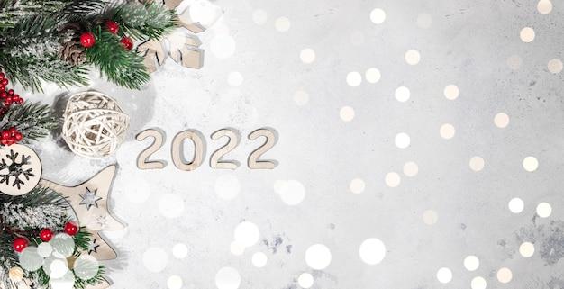 Bannière de bonne année 2022, fond clair de nouvel an décoré de branches de sapin, de boules de noël rouges et de lumières, fond de lumières bokeh avec un espace libre pour le texte