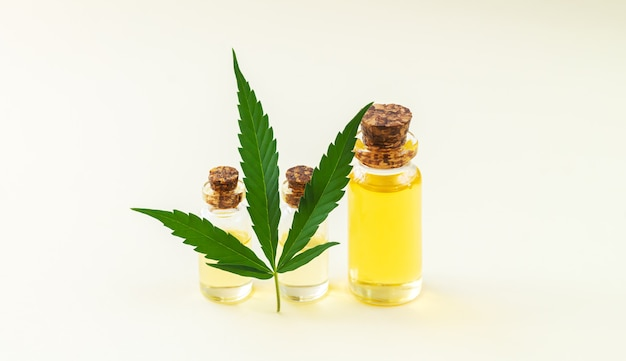 Bannière de bouteilles en verre d'huile de chanvre et de feuilles de cannabis en gros plan