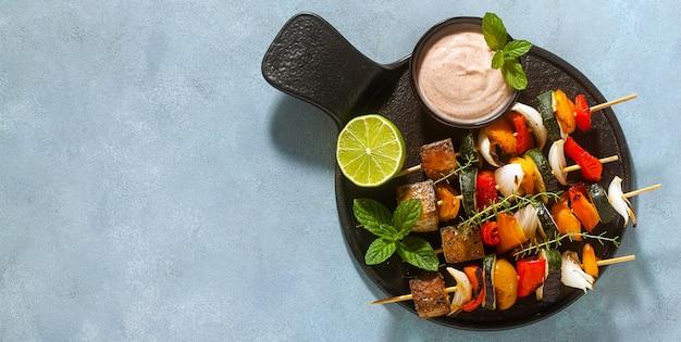 Bannière de brochettes de légumes végétaliens prêts et tofu fumé avec sauce aux noix de cajou et paprika fumé sur fond bleu