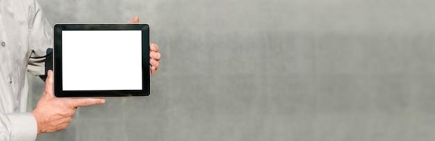 Bannière close up, mock up tablet, présentation du plan d'affaires, mains de l'homme. sur fond de mur de béton.