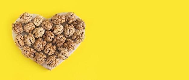 Bannière de coeur de noix sur un fond minimal jaune.