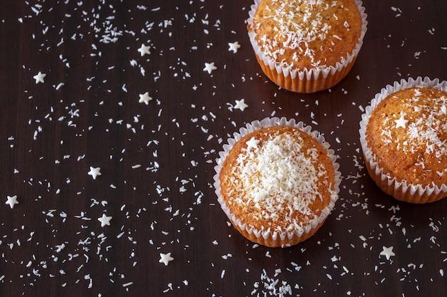 Bannière de concept de nouvel an et de noël avec fond sombre de muffin à la noix de coco maison. vue de dessus. mise au point sélective.