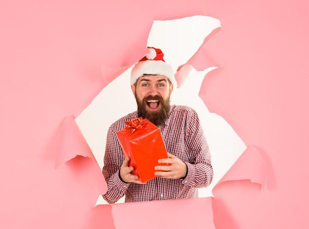 Bannière de conception d'affiches de vacances de noël santa man regardant à travers le trou dans le papier avec une boîte-cadeau actuelle