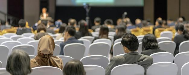Bannière de couverture de vue arrière de l'audience à l'écoute. intervenants sur la scène dans la salle de conférence.