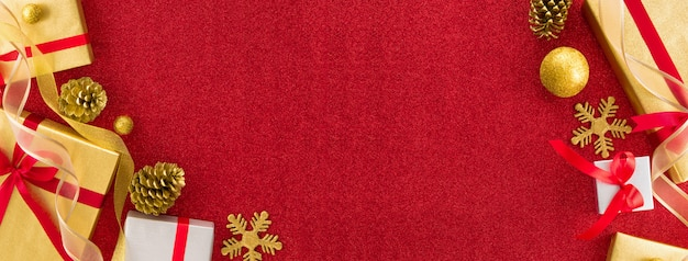 Bannière design de frontière de noël avec des boîtes en or et en argent arrondies par un ruban rouge et du papier brillant pour des décorations