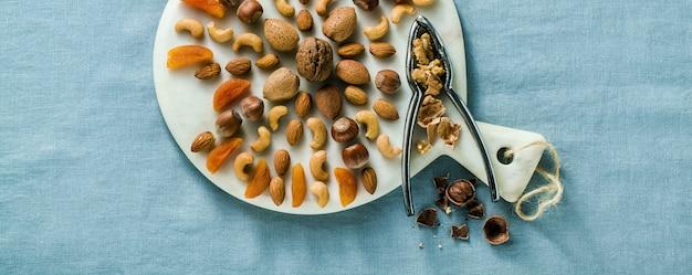 Bannière de divers types de fruits secs et de noix sur une planche à découper en marbre sur une nappe en lin bleu