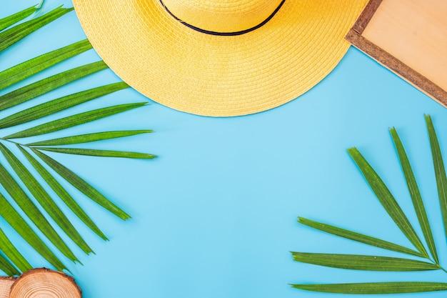 Bannière d'été bleu avec chapeau jaune, lunettes de soleil, coquillage, cadre et feuille de palmier