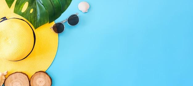 Bannière d'été bleu avec chapeau jaune, lunettes de soleil, coquillage et feuille de monstera