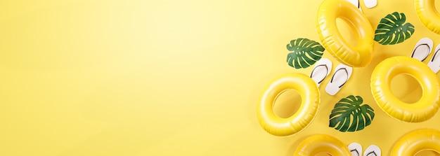 Bannière d'été fond jaune. tongs, feuille et anneau de natation gonflable copie espace rendu 3d