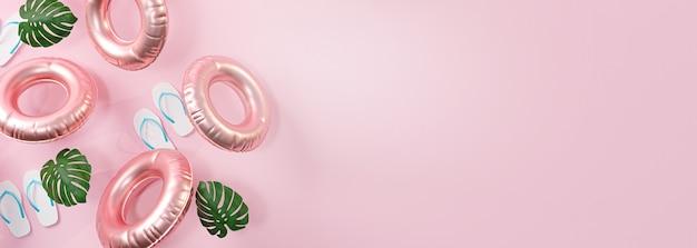 Bannière d'été fond rose. tongs, feuille et anneau de natation gonflable copie espace rendu 3d