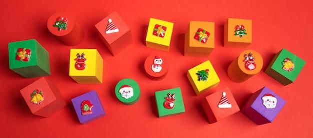 Bannière festive avec des jouets mous cubes pour enfants multicolores avec des symboles de noël dessus sur fond rouge. arrangement de décorations de noël. vue de dessus.
