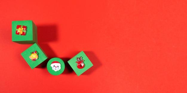Bannière festive avec quatre cubes verts pour enfants en peluche avec des symboles de noël au-dessus d'eux sur fond rouge. décorations de noël. vue d'en-haut. copiez l'espace pour le texte.