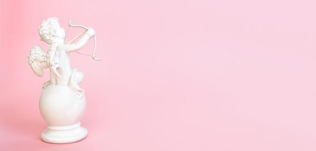 Bannière. figurine d'un ange cupidon avec un arc sur fond rose. la saint-valentin. copier l'espace