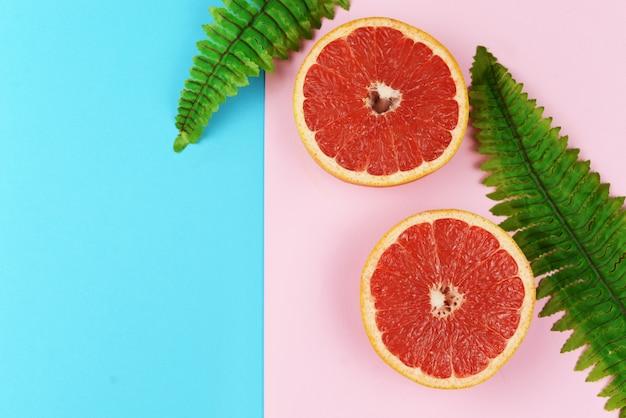 Bannière de fond avec des fruits exotiques citron vert pamplemousse et feuilles de palmier vert