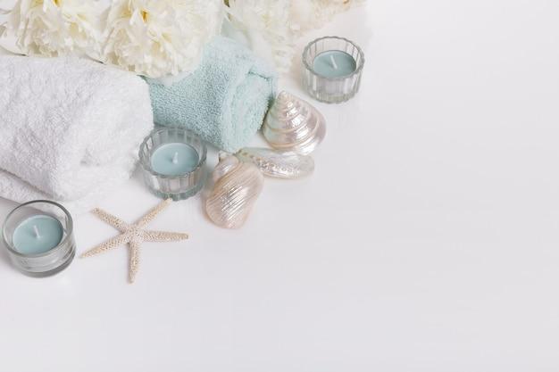 Bannière de fond de printemps ou d'été doux avec fleurs de pivoine et coquillages, bougies, sel de spa sur blanc