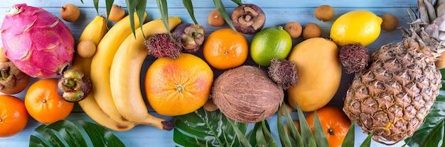 Bannière de fruits tropicaux arc en ciel en bonne santé avec des feuilles de palmier sur une table en bois bleue