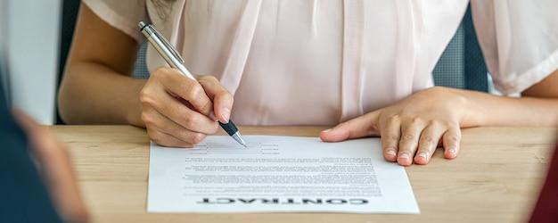 Bannière de gros plan jeune femme asiatique diplômée signant le contrat après l'entretien d'embauche