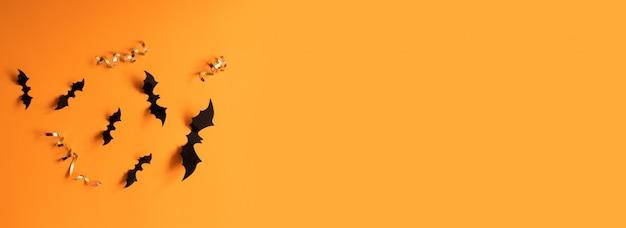 Bannière d'halloween avec des chauves-souris noires sur une surface orange, vue de dessus.