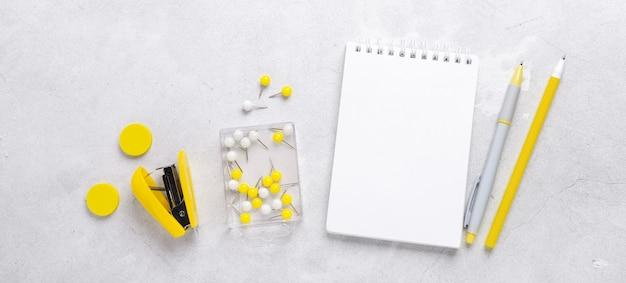 Bannière horizontale. lieu de travail de bureau. bloc-notes avec stylo et autocollant jaune sur fond de pierre grise. mise à plat. vue de dessus