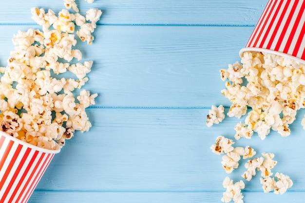 Bannière horizontale de pop-corn. coupe de papier dépouillé rouge et les noyaux se trouvant sur un fond en bois bleu.