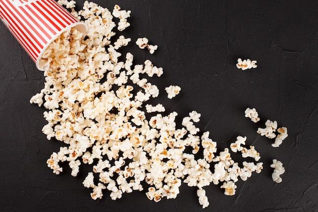Bannière horizontale de pop-corn. gobelet en papier rayé rouge et grains se trouvant sur un fond sombre.