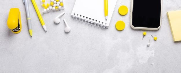Bannière horizontale avec smartphone, bloc-notes et accessoires de papeterie jaunes sur fond de pierre grise. illuminating yellow et ultimate grey, couleurs de l'année 2021 - image