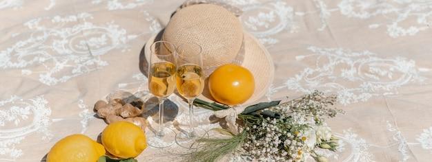 Bannière horizontale ou en-tête avec deux verres à vin blanc sur une couverture avec des fleurs, un chapeau de paille et des fruits tropicaux autour.