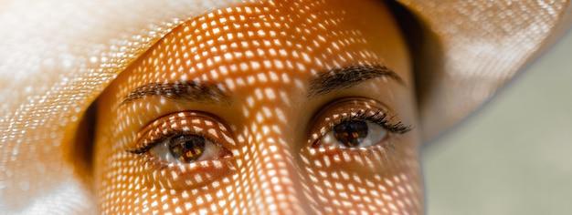 Bannière horizontale ou en-tête gros plan femme yeux marron regardant la caméra avec une ombre de chapeau.