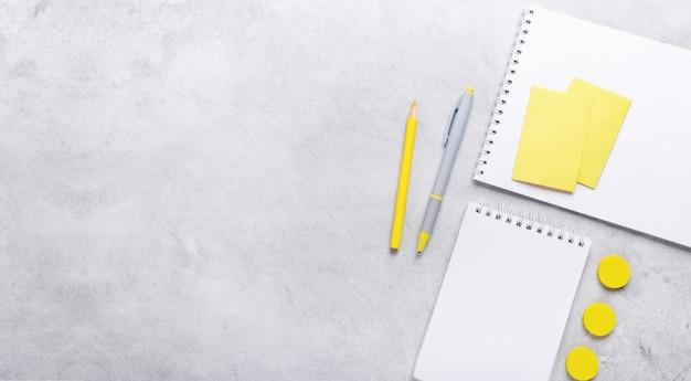 Bannière horizontale. vue de dessus de l'espace de travail avec bloc-notes et accessoires de papeterie sur fond de pierre grise. illuminating yellow et ultimate grey, couleurs de l'année 2021