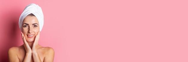 Bannière de jeune femme souriante avec une serviette sur la tête, épaules nues sur fond rose