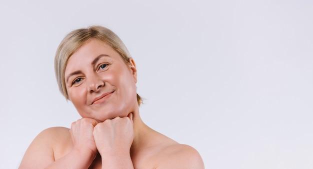 Bannière. une jolie femme senior avec une peau saine et hydratée regarde la caméra et souriant