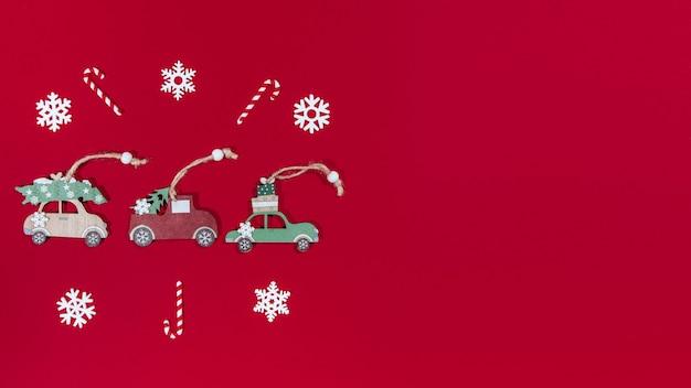 Bannière de jouets de noël voitures, flocons de neige, bonbons, sur un arbre de noël sur fond rouge