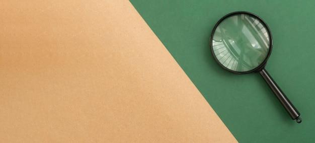 Bannière kraft en carton brun avec espace de copie et loupe sur fond vert