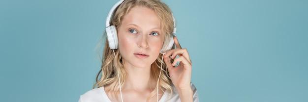 Bannière longue largeur avec portrait de jeune femme écoutant de la musique via un casque