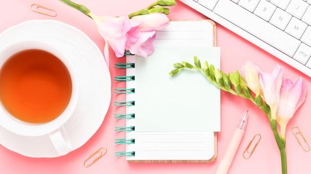 Bannière de maquette de feuille vide avec tasse de thé clavier freesia fleurs roses sur fond rose