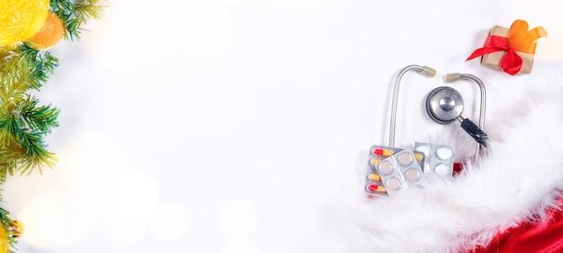 Bannière médicale avec pilules, boîte cadeau, stéthoscope et arbre de noël sur blanc