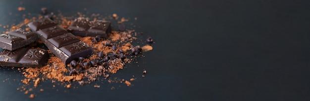 Bannière de morceaux de barre de chocolat amer cassé et poudre de cacao sur une surface sombre