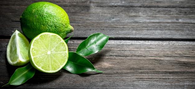 Bannière avec des morceaux de citron vert frais avec des feuilles sur table rustique