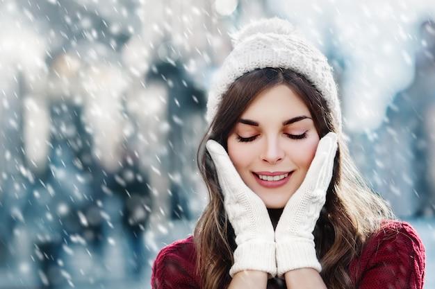 Bannière de neige d'hiver avec belle fille souriante et portant des lueurs