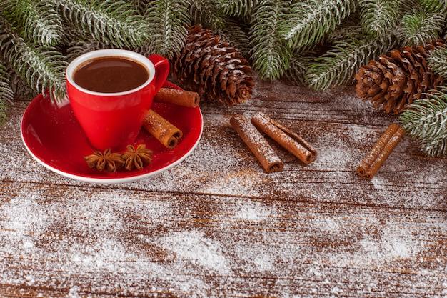 Bannière de noël avec arbre vert, cônes, tasse rouge au chocolat chaud, décorations rouges, cannelle