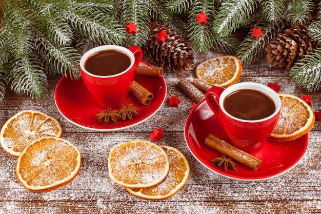 Bannière de noël avec arbre vert, cônes, tasses rouges au chocolat chaud, orange et cannelle.