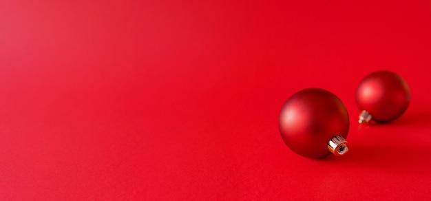 Bannière de noël avec des boules de noël sur une surface rouge